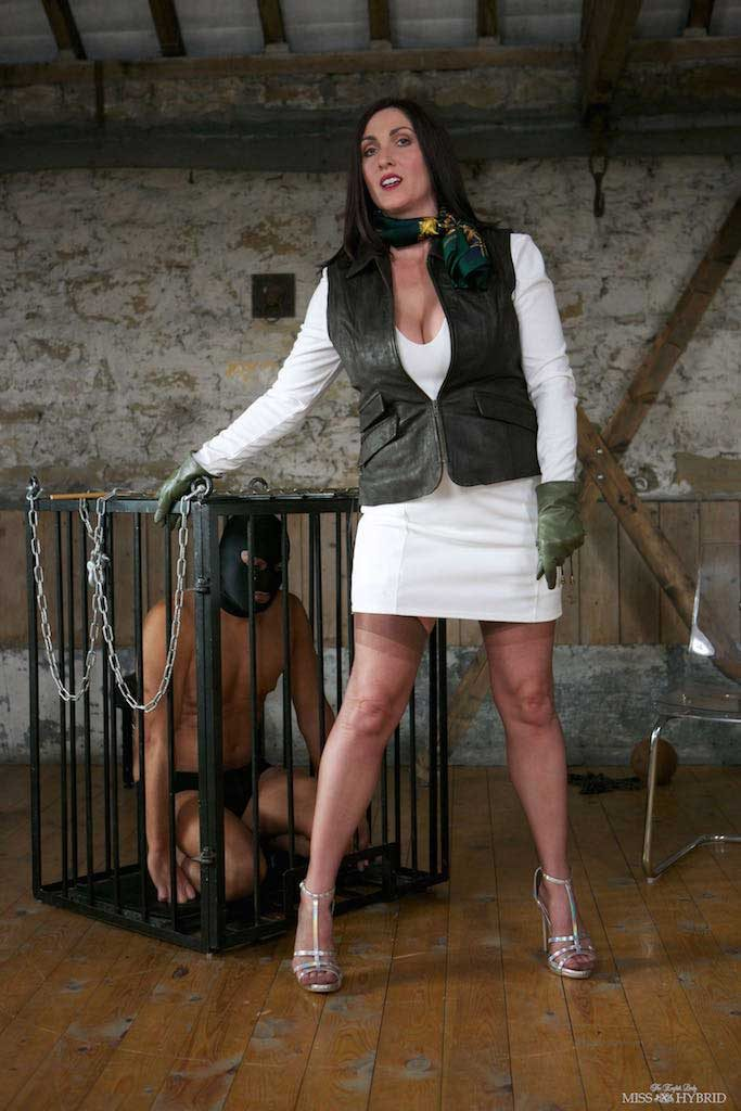 Miss Hybrid in the manor dungeon in nylons, suspenders and leather gloves.