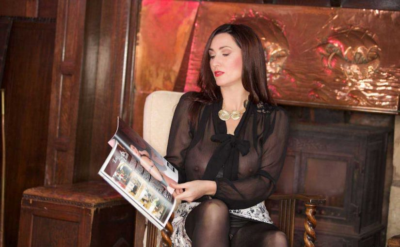 Miss Hybrid crotchless pantyhose and sheer blouse reading her fetish magazine.