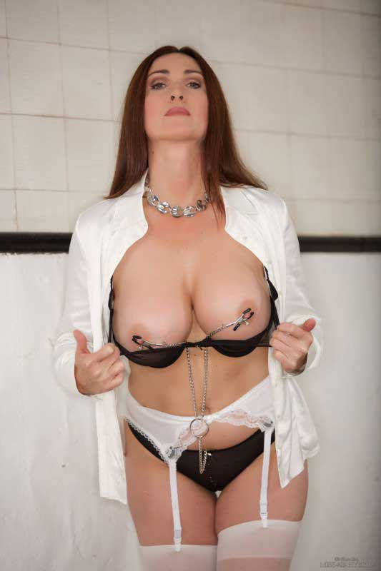 Miss Hybrid clamped nipples, stockings and stilettos.