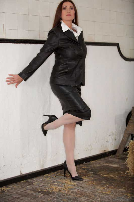 Miss Hybrid stunning in leather jacket, leather skirt, stockings and stilettos.